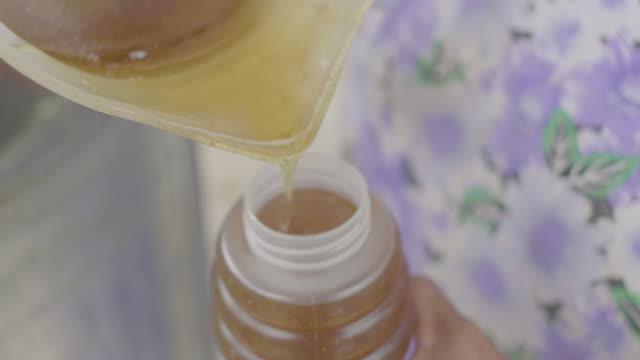 plastic jug full of honey poured into a plastic jar - south america stock-videos und b-roll-filmmaterial