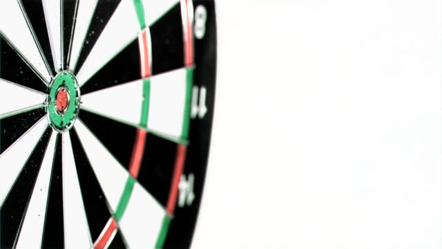 plastic red dart in super slow motion being thrown on a dart board - dart board stock videos & royalty-free footage