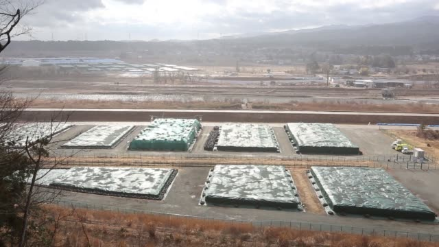plastic sheets cover radioactive contaminant soil in naraha fukushima prefecture japan on sunday feb 14 a geiger counter is seen outside the site... - contatore geiger video stock e b–roll