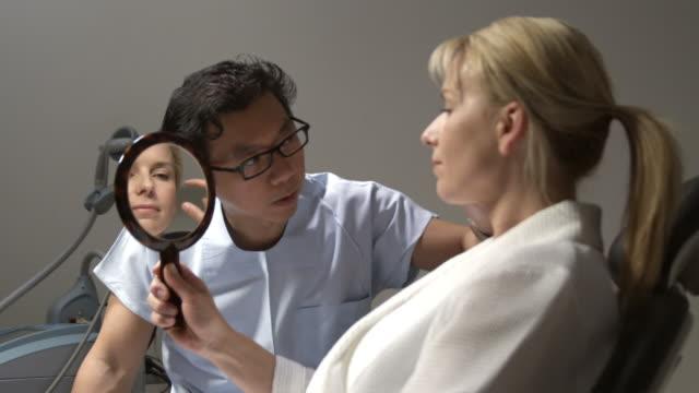 vídeos de stock, filmes e b-roll de cu, pan, plastic surgeon in operating room in pre-surgery consultation with woman looking into hand-held mirror, sydney, australia - cirurgia plástica