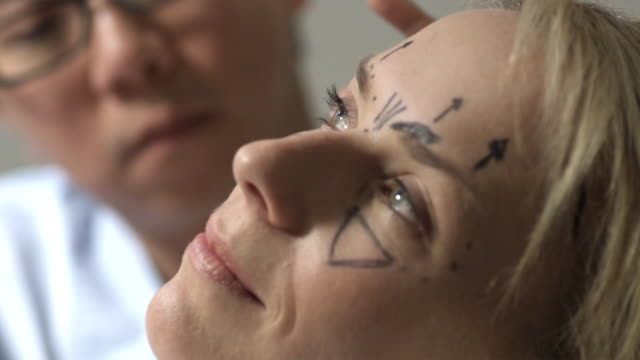 ecu, selective focus, plastic surgeon in operating room marking woman's face with surgical marker for surgery, sydney, australia - plastic surgery stock videos and b-roll footage