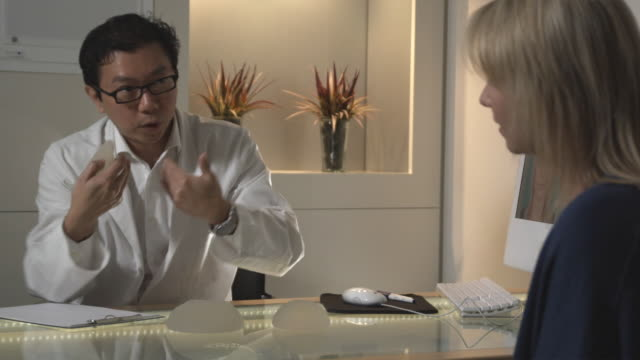 MS, Plastic surgeon showing breast implant to patient in office, Sydney, Australia