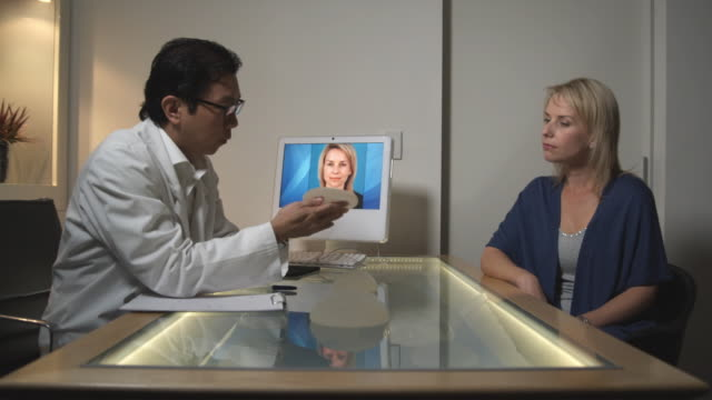 vídeos de stock e filmes b-roll de ms, plastic surgeon showing breast implants to patient in office, sydney, australia - tratamento a laser