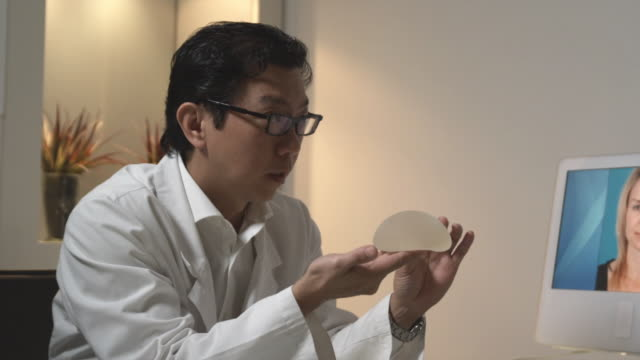 MS, PAN, Plastic surgeon showing breast implants to patient in office, Sydney, Australia