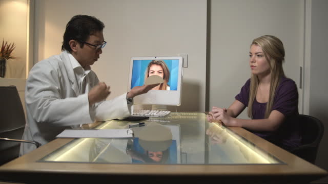 MS, Plastic surgeon showing breast implants to patient in office, Sydney, Australia