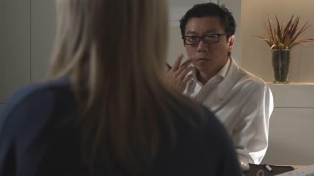 vídeos de stock, filmes e b-roll de ms, pan, plastic surgeon talking to female patient in office, sydney, australia - cirurgia plástica