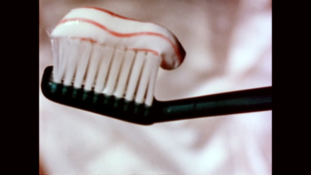 CU of plastic toothbrush / toothpaste squeezed onto brush Toothpaste on toothbrush on January 01 1958