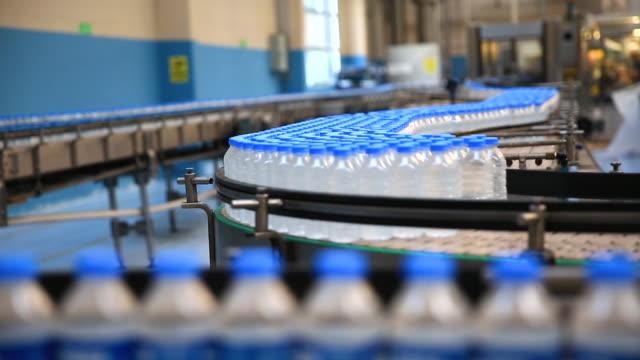 plastic water bottles in factory on conveyor belt production - bottiglia video stock e b–roll