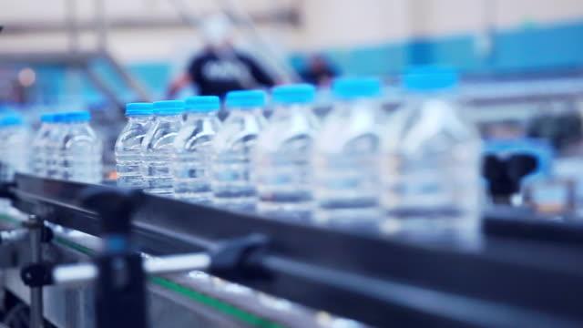 plastic water bottles in factory on conveyor belt - water bottle stock videos & royalty-free footage