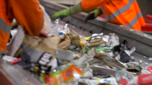 plastics refuse and garbage on conveyor belts being sorted bags and other recycling waste sorted - 廃棄物処理点の映像素材/bロール