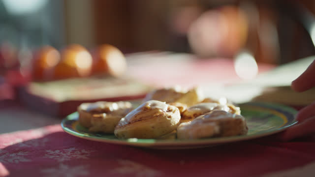 cu plate of cinnamon buns are picked up and then put back down on the table - freshness stock videos & royalty-free footage