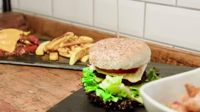 vídeos de stock e filmes b-roll de prato de comida deliciosa e hamburger - pimenteiro de mesa