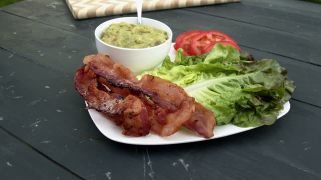 a plate of guacamole, bacon, tomato and lettuce on a rustic wooden table all set up for a picnic dinner of beef or chicken - low carb diet stock videos & royalty-free footage