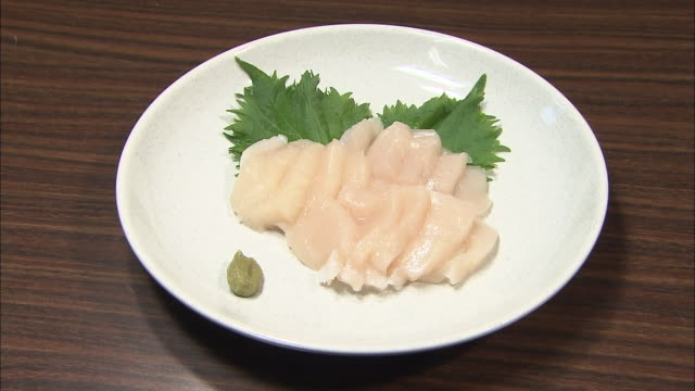 A plate of raw scallops is served on a plate with a garnish and condiment