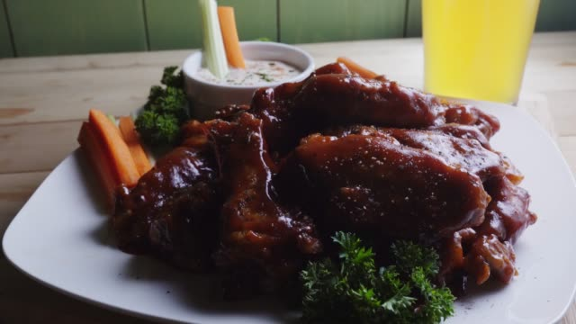 a plate of saucy baked grilled chicken wings accompanied by hot sauce celery and carrot sticks and a cold beer - ranch dip stock videos & royalty-free footage