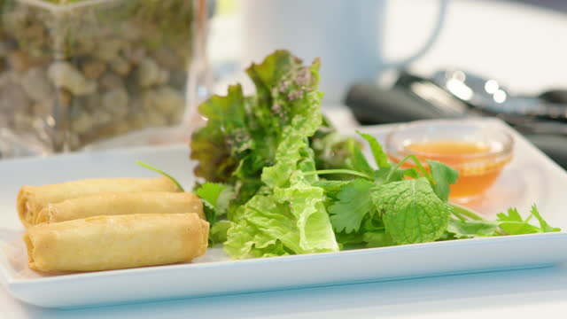 plate of spring rolls with garnish being served by waiter - garnish stock videos & royalty-free footage