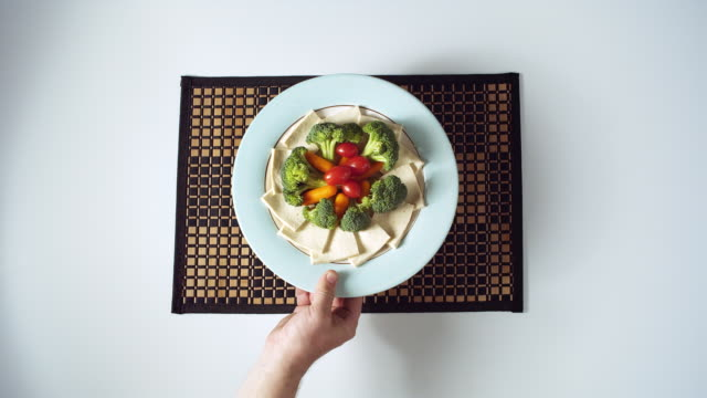 MS HA Plate with vegetables and tofu artfully arranged being served onto mat
