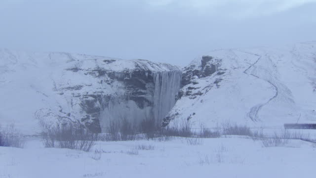 plateau waterfall water falling over flat area between snowy mountains w/ snow covered land & dried frozen vegetation patches fg, waterfall, xws... - frozen water stock videos & royalty-free footage
