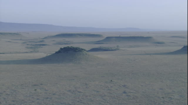 Plateaus rise above the savannah in the Maasai Mara in Kenya. Available in HD.