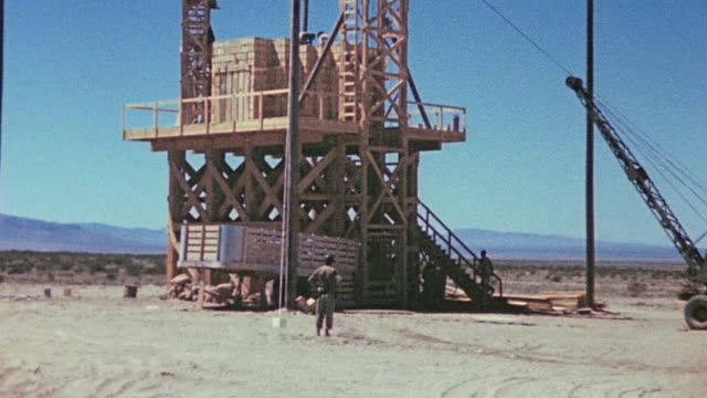 platform constructed for the pretest calibration explosion with mobile crane to one side and 108 tons of tnt spiked with fission products stacked in... - white sands missile range stock videos & royalty-free footage