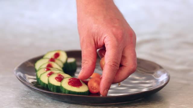 vídeos de stock, filmes e b-roll de plating cucumber, chili sauce and tomatoes - comida salgada