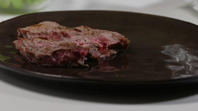 plating grilled steak. - annick vanderschelden stock videos & royalty-free footage