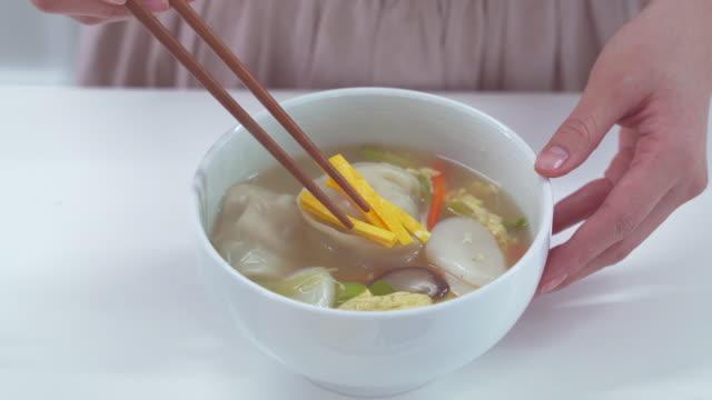 plating tteok mandu guk (korean rice cake soup with dumplings) - korean new year stock videos & royalty-free footage