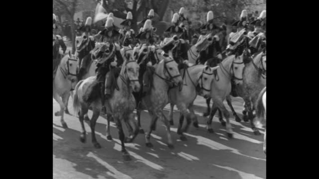 platoon of mounted buglers rides by / ws review stand mounted officers and tree lined road into parade ground regiments march by - platoon stock videos and b-roll footage