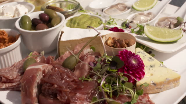 platter compiled of breads dips olives oysters cured meats nuts cheese mussels filled bell peppers caperberries onion relish includes unidentified... - italian food stock videos & royalty-free footage