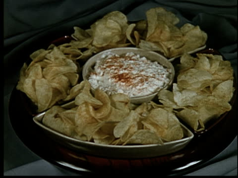 1955 cu platter of potato chips with bowl of cottage cheese in center/ man's hand dipping chip in cottage cheese - 塩味スナック点の映像素材/bロール
