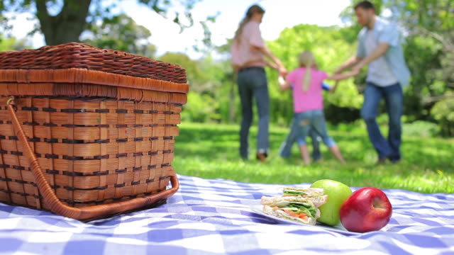 vidéos et rushes de family together in the background with a platter on a picnic basket in the foreground - panier de pique nique
