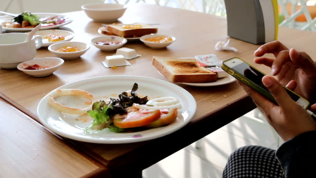 play smartphone while eating breakfast. - service occupation stock videos and b-roll footage