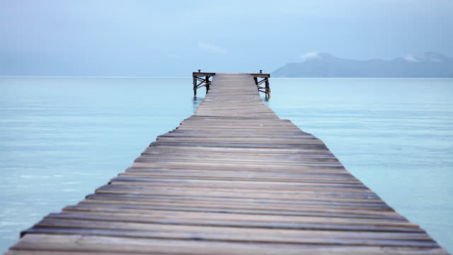 Playa de Muro with idyllic long wooden jetty in caribbean coloured waters and mountain range in background
