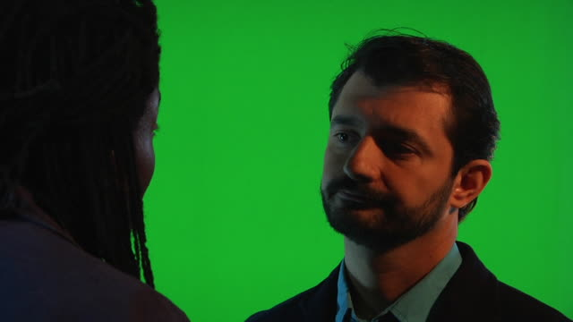 different shots in front of the green screen of woman talking to a man complaining while the man comforts her - chroma key stock videos & royalty-free footage