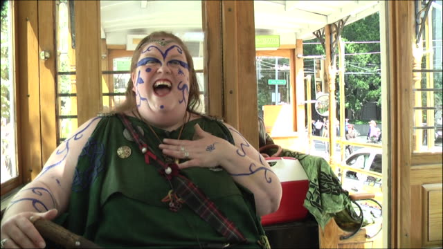interview of pride parade participant, woman in green dress and blue facepaint, talking about why she's attending pride weekend and how she likes... - participant stock videos & royalty-free footage