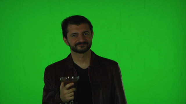 man in leather jacket holding a wine glass standing in front of greenscreen, gestures to the camera and takes a sip - gesturing stock videos & royalty-free footage
