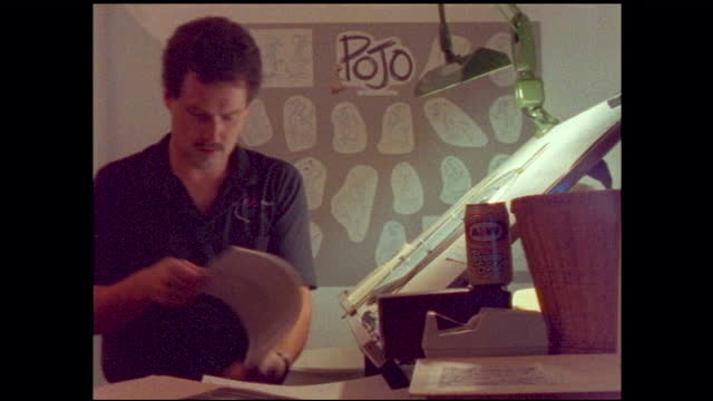 """stable time lapse view of man drawing in front of drawing board; board on the wall """"pojo"""" - animator stock videos & royalty-free footage"""