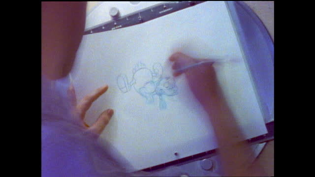 woman talking and smiling to the camera in front of cartoon backdrop; man drawing in front of the drawing board - アニメーター点の映像素材/bロール