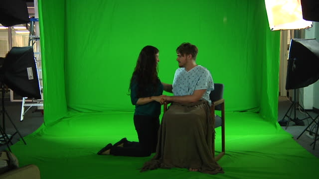 woman with man in patient costume sitting on chair in front of greenscreen, woman kneels to comfort him; no sound; woman and man lying on the bed - chroma key stock videos & royalty-free footage