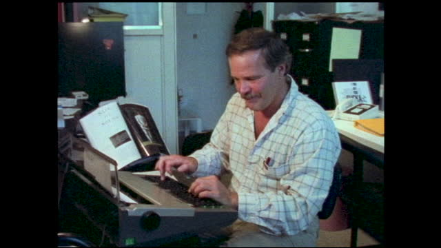 "zoom in views of man typing at typewriter inside office; zoom in of framed artwork with logo on store window ""animania cartoon studio"" - animator stock videos & royalty-free footage"