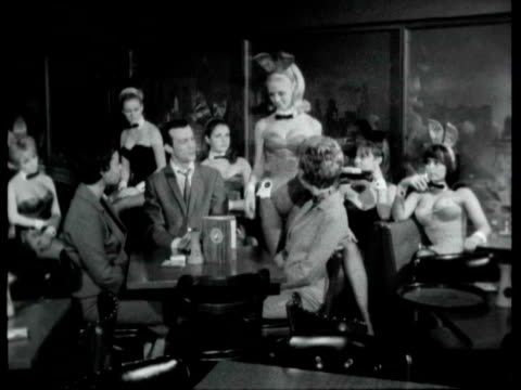 playboy bunny girl serving drinks to customers at table / bunny girl demonstrating the bunny dip as man describes what she is doing hugh hefner's... - 1966 stock videos & royalty-free footage