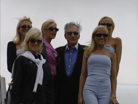 playboy founder hugh hefner poses with various promotional staff on the steps of his private aircraft after flying into heathrow from cannes group... - playboy magazine stock videos & royalty-free footage