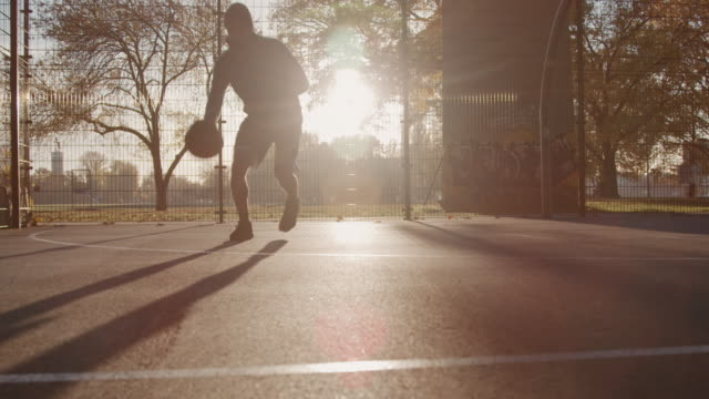 vidéos et rushes de joueur à dribbler le ballon sur cour au coucher du soleil - streetball