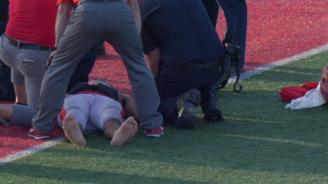 a player is injured with an injury with a paramedic helping at an american football game. - brain damage stock videos & royalty-free footage