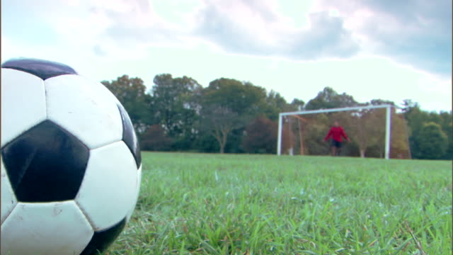 Player kicking ball to goalie