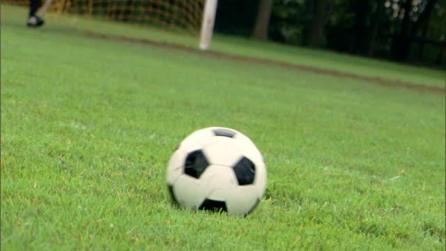 Player kicking soccer ball to goalie