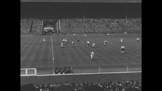 stockvideo's en b-roll-footage met player scoops ball out of goal kicks it away as vo excited crowd at 1953 football association cup final game between bolton wanderers and blackpool /... - fa cup