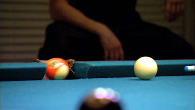 mcu player sinking stripe 13 orange ball into side pocket taking aim striking white cue ball toward frame sinking solid 8 ball black in corner pocket... - hosentasche stock-videos und b-roll-filmmaterial