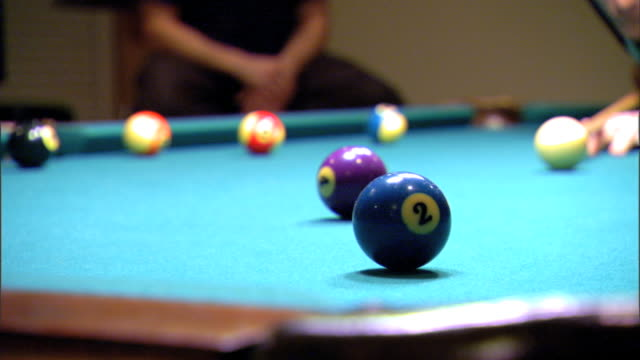 player taking aim striking white cue ball hitting solid 2 blue ball aiming for corner pocket in fg missing other balls scattered on pool table... - cue ball stock videos & royalty-free footage