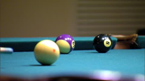 player taking aim, striking white cue ball & hitting stripe 11 red ball, aiming for far corner pocket of pool table, missing. cue sports, cuesports - キューボール点の映像素材/bロール